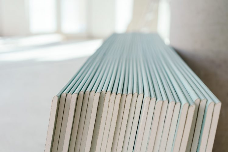 Large stack of white chip board against a wall in an empty new build property in a close up view
