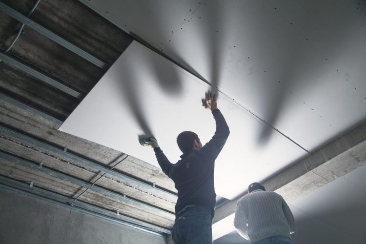 Workers fitting panel into frame of ceiling.