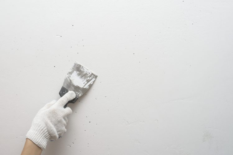 Working tool, spatula in hand against the background of a white wall, work plasterer. Putty walls with their own hands.